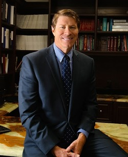 Dr. Lane Smith seated on his desk at Smith Plastic Surgery